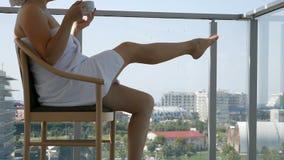 Szczęśliwa kobieta W Bathrobe Po tym jak zdroju traktowania komesi balkon Piją kawę zbiory