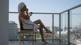 Szczęśliwa kobieta W Bathrobe Po tym jak zdroju traktowania komesi balkon Piją kawę zdjęcie wideo