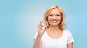 Szczęśliwa kobieta w białej koszulce pokazuje ok ręka znaka Obrazy Royalty Free