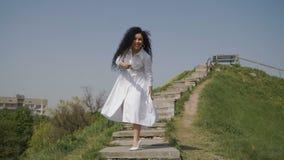 Szczęśliwa kobieta w biel długiej sukni pozuje dla kamery przy schodkami na zielonym wzgórzu zdjęcie wideo