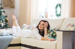 Szczęśliwa kobieta w biel dziam być ubranym relaksuje w domu dla bożych narodzeń zdjęcia royalty free