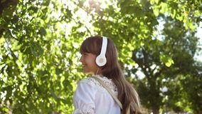Szczęśliwa kobieta w biel sukni z długie włosy podróżami wokoło miasta swobodny ruch dziewczyna z plecakiem chodzi w parku z zbiory