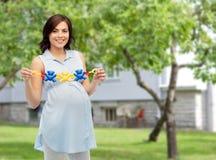 Szczęśliwa kobieta w ciąży mienia brzęku zabawka Zdjęcia Stock