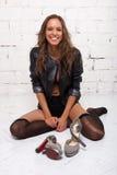 Szczęśliwa kobieta w czarnej kurtce na podłoga przed ona buty Biały ściana z cegieł, odizolowywający zdjęcie royalty free