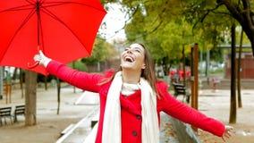 Szczęśliwa kobieta w czerwieni cieszy się pod deszczem zdjęcie wideo