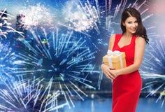 Szczęśliwa kobieta w czerwieni sukni z prezentem nad fajerwerkiem Obraz Stock