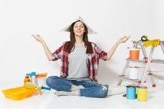 Szczęśliwa kobieta w gazetowym kapeluszowym obsiadaniu na podłogowy medytować, robić joga, relaksuje z instrumentami dla odświeża zdjęcia stock