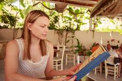 Szczęśliwa kobieta w kawiarni z menu Piękna urlopowa kobieta w restauraci przy gościem restauracji Zdjęcia Stock