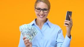 Szczęśliwa kobieta w kostiumu z smartphone pokazuje wiązkę dolary, online biznes zdjęcie wideo
