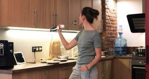 Szczęśliwa kobieta w kuchni śpiewa i tanczy zbiory wideo
