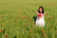 Szczęśliwa kobieta w kwiatonośnym maczka polu outdoors z maczka bukietem fotografia stock