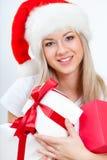 Szczęśliwa kobieta w Santa kapeluszowym mienia prezencie boksuje Obrazy Royalty Free