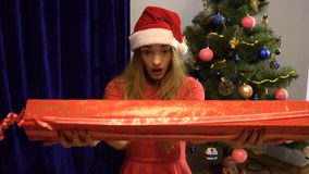 Szczęśliwa kobieta w Santa kapeluszu z dużym długim boże narodzenie prezentem pokazuje aprobaty zdjęcie wideo