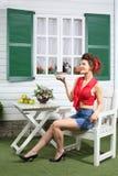 Szczęśliwa kobieta w skrótach siedzi przy stołowym następnym dom na wsi zdjęcia stock