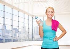 Szczęśliwa kobieta z butelką woda i ręcznik w gym Fotografia Stock