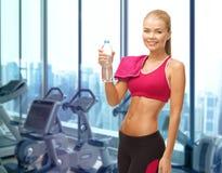 Szczęśliwa kobieta z butelką woda i ręcznik w gym Zdjęcie Royalty Free