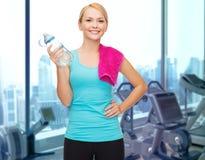 Szczęśliwa kobieta z butelką woda i ręcznik w gym Obraz Stock