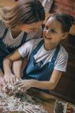 Szczęśliwa kobieta z córki kulinarnym ciastem zdjęcie stock