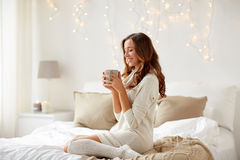 Szczęśliwa kobieta z filiżanką kawy w łóżku w domu zdjęcia royalty free