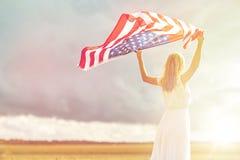Szczęśliwa kobieta z flaga amerykańską na zboża polu zdjęcia royalty free