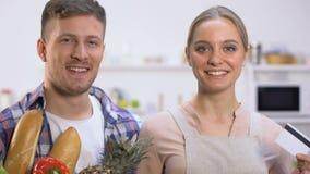 Szczęśliwa kobieta z kartą kredytową, mężczyzny mienia świeża żywność w torbie na zakupy, dostawa zbiory wideo