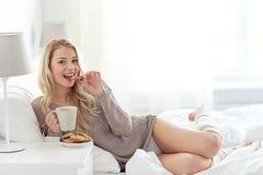 Szczęśliwa kobieta z kawą i ciastkami w łóżku w domu zdjęcia stock