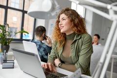 Szczęśliwa kobieta z komputerowym działaniem przy biurem zdjęcie royalty free