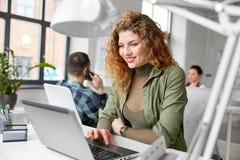 Szczęśliwa kobieta z komputerowym działaniem przy biurem zdjęcia stock