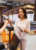 Szczęśliwa kobieta z kredytowej karty kupienia jedzeniem w rynku Fotografia Royalty Free