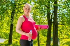 Szczęśliwa kobieta z matą i butelką woda fotografia royalty free