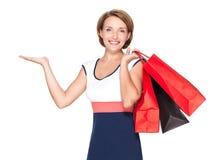 Szczęśliwa kobieta z prezentacj torba na zakupy i gestem Obraz Stock