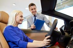Szczęśliwa kobieta z samochodowym handlowem w auto przedstawieniu lub salonie Zdjęcia Royalty Free