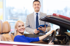 Szczęśliwa kobieta z samochodowym handlowem w auto przedstawieniu lub salonie Obraz Stock