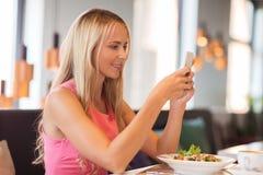 Szczęśliwa kobieta z smartphone łasowaniem przy restauracją Zdjęcia Stock