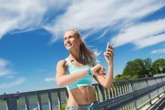 Szczęśliwa kobieta z tętna smartphone i zegarkiem Obraz Stock