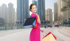 Szczęśliwa kobieta z torba na zakupy nad Dubai miastem zdjęcie royalty free