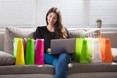 Szczęśliwa kobieta Z torba na zakupy Używać laptop zdjęcia royalty free