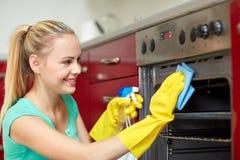 Szczęśliwa kobiety cleaning kuchenki kuchnia w domu Fotografia Stock