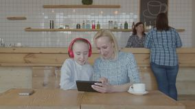 Szczęśliwa kobiety i preteen dziewczyna skyping w bufecie zdjęcie wideo
