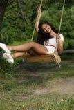 Szczęśliwa kobiety jazda na huśtawce w parku fotografia stock