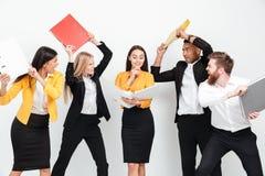 Szczęśliwa kobiety mienia falcówka podczas gdy gniewny kolegów walczyć obrazy stock
