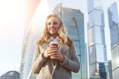 Szczęśliwa kobiety mienia kawa na drapacza chmur tle w jesień dniu Zdjęcia Stock