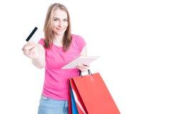 Szczęśliwa kobiety mienia pastylka z torba na zakupy oferuje debetowego samochód Obrazy Stock