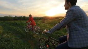 Szczęśliwa kochająca para ma zabawę podczas gdy jadący bicykle wzdłuż kwitnienia pola podczas zmierzchu Romantyczna atmosfera zbiory