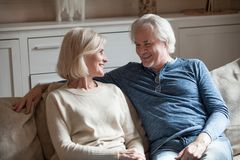 Szczęśliwa kochająca starsza para opowiada relaksować na kanapie wpólnie fotografia stock