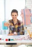 Szczęśliwa krawiecka kobieta pokazuje nożyce obrazy stock