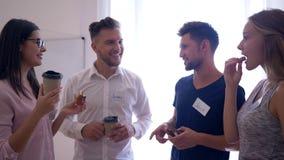 Szczęśliwa kreatywnie drużyna komunikuje i pijący kawę z cynamonowymi babeczkami podczas przerwy w biurze zbiory wideo