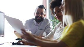 Szczęśliwa kreatywnie drużyna opowiada w biurze z papierami zbiory