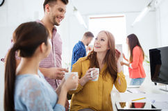 Szczęśliwa kreatywnie drużyna pije kawę przy biurem Obraz Stock