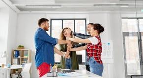 Szczęśliwa kreatywnie drużyna pokazuje aprobaty przy biurem zdjęcia stock